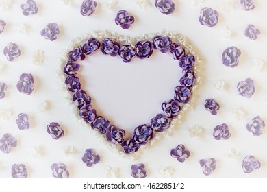 Festive background with hearts of flowers. Valentine's Day background. Frame of flowers of lilac. The top view. Flat lay. Vintage style and vignette.