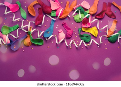 Festive background of purple material colorful balloons streamers confetti. Top view flat lay copy space toning