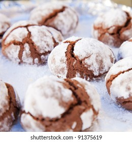 festive baking  - chocolate cookies with icing sugar coating ona baking tray