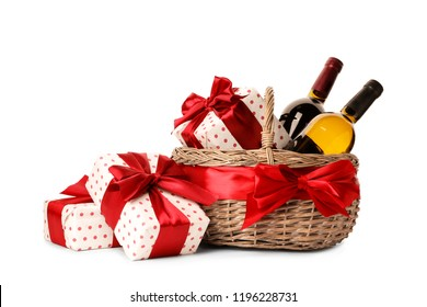 Festive basket with bottles of wine and gifts on white background