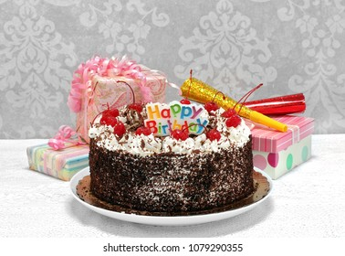 Festive Black Forest Chocolate Happy Birthday Cake with gifts and party horns.  Close up with copy space.