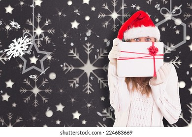 Festive blonde holding a gift against snowflake wallpaper pattern