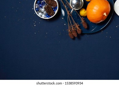 festive blue table, top view with free space, with blue plate, pumpkin, quince, pepper pot  and Christmas tree toys, all in gold sequins in the form of stars