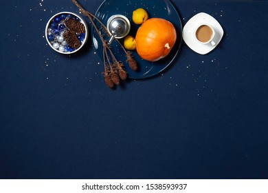 festive blue table, top view with free space, with blue plate, pumpkin, quince, pepper pot, coffee Cup and Christmas tree toys, all in gold sequins in the form of stars