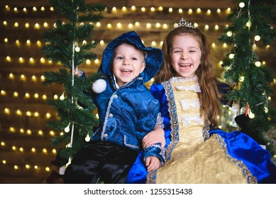 festive boy and girl in blue on christmas seesaw