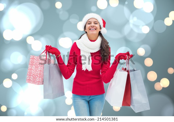 Festive brunette holding shopping bags against white glowing dots on blue