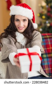 Festive brunette showing gift at christmas at home in the living room