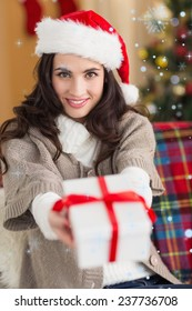 Festive brunette showing gift at christmas against snow falling