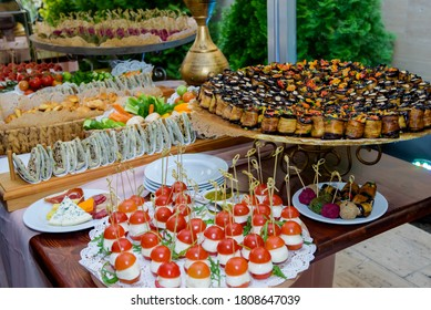 Festive Buffet table of reception with cold snacks, meat and seafood canapes. oriental salads. And sweet candy bar