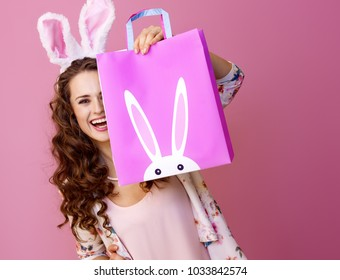 Festive bunny and eggs season. happy modern woman in Easter bunny ears isolated on pink hiding behind Easter shopping bag