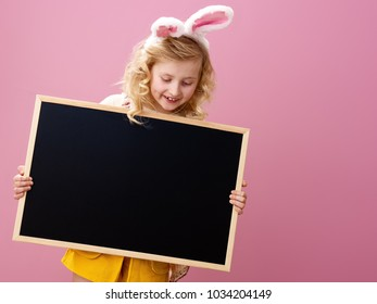 Festive bunny and eggs season. happy modern girl in Easter bunny ears on pink background looking at blank board