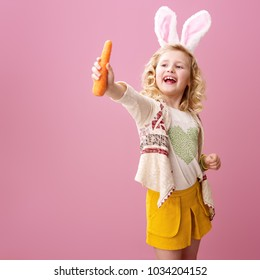 Festive bunny and eggs season. happy modern child in Easter bunny ears isolated on pink showing carrot