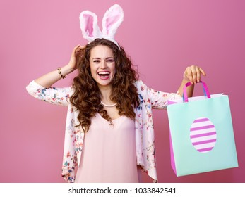 Festive bunny and eggs season. Portrait of cheerful stylish woman in Easter bunny ears isolated on pink background with Easter shopping bag