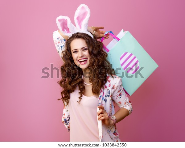 Festive bunny and eggs season. Portrait of smiling stylish woman in Easter bunny ears on pink background with Easter shopping bag