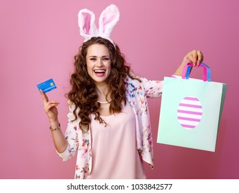 Festive bunny and eggs season. smiling trendy woman in Easter bunny ears isolated on pink background with Easter shopping bag and credit card