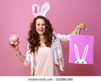 Festive bunny and eggs season. smiling young woman in Easter bunny ears isolated on pink background with Easter shopping bag and piggy bank