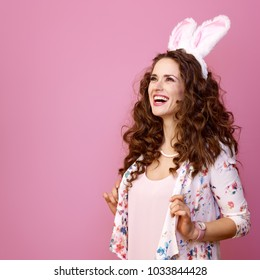 Festive bunny and eggs season. smiling modern woman in Easter bunny ears isolated on pink background looking at copy space