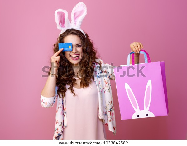 Festive bunny and eggs season. smiling modern woman in Easter bunny ears isolated on pink with Easter shopping bag and credit card