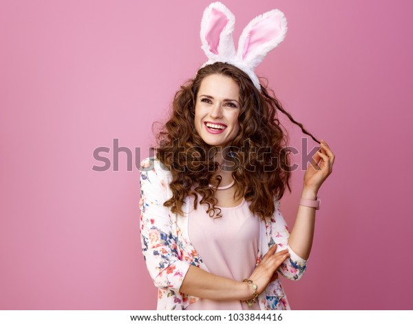 Festive bunny and eggs season. smiling stylish woman in Easter bunny ears isolated on pink background looking at copy space