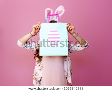 Festive bunny and eggs season. young woman in Easter bunny ears on pink background hide behind Easter shopping bag