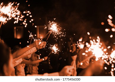 festive burning bright sparklers in the hands of guests at a party