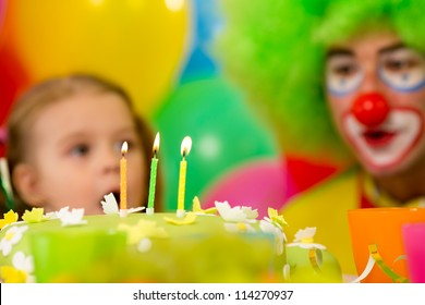 festive cake with three candles and kid with clown on background
