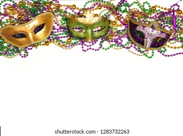 Festive Carnival background with masks, beads and copy space. Carnivale mask on a white background.