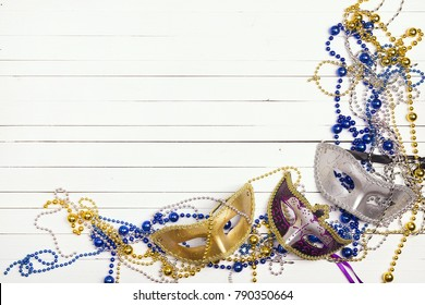 Festive Carnival background with masks, beads and copy space on wooden table. Carnivale mask on a white background.