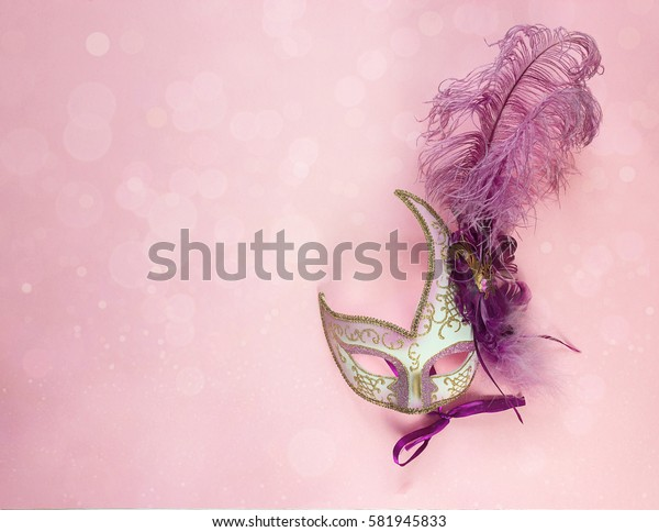 Festive Carnival Background with masks with feathers and copy space. Carnival mask on a pink background.