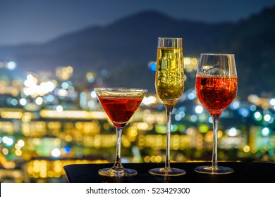 festive celebration background and texture , cocktail glass of rose wine, bottle of wine and dicoration on dark stone table blurred bokeh background