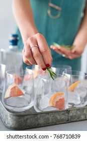 Festive celebration drinks woman at party making a tray of gin and tonics with rosemary and grapefruit
