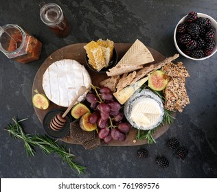 Festive cheeseboard with a variety of cheeses, crackers, fruit, honey, rosemary sprigs and chutney.