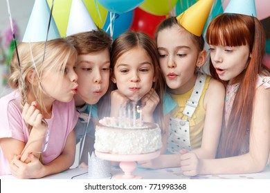 Festive children in party caps, blow candles on delicious cake, make wish, celebrate birthday, have party together, hold colourful balloons. Happy small girl spends festive event with best friends