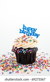 Festive Chocolate Cupcake Topped with Colorful Sprinkles and Happy Birthday Sign on White Background