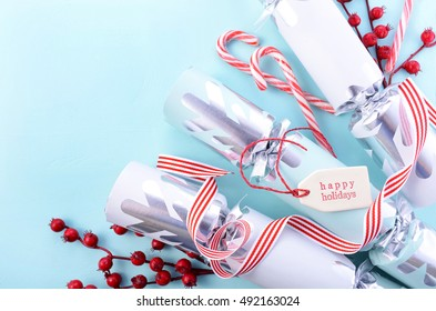 Festive Christmas background with decorated borders of red and white candy canes, bon-bons, berries and Happy Holidays gift tag on a pale blue wood table. Negative copy space.