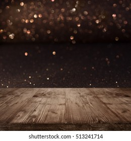 Festive Christmas background with shimmering light and bokeh in front of a wooden table