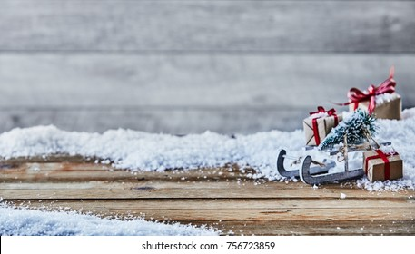 Festive Christmas background with winter snow on rustic wood with space for product placement and a side arrangement of sled, tree, and gifts with soft blur background copy space