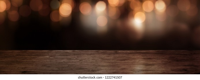 Festive christmas background with wooden table and golden bokeh