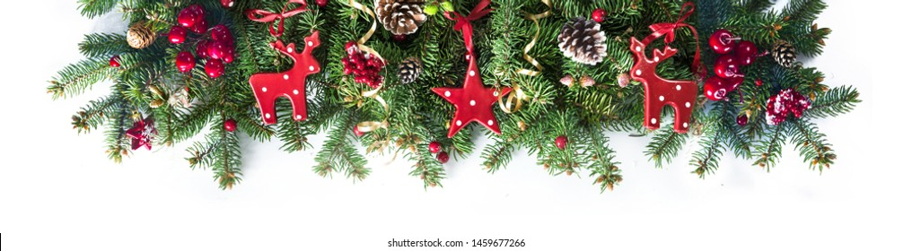 Festive Christmas border, isolated on white background. Fir green branches are decorated with red stars, berries, fir cones and red toy deer, close-up.