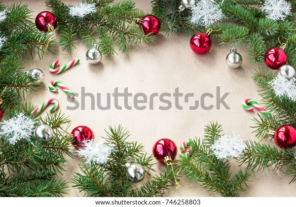 Festive christmas border with red and silver balls on fir branches and snowflakes on rustic beige background with copyspace