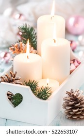Festive Christmas decoration with four Advent candles in a white shabby chic tray with fit branches, pine cones. Shallow depth of field, selective focus on central candles
