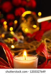Festive Christmas decoration with one burning candle and brass instrument in the background