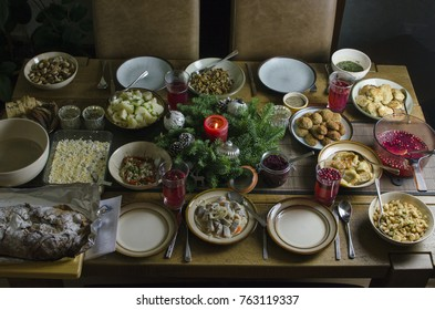 A festive Christmas Eve dinner table with many dishes, candle and Christmas decorations, traditional Lithuanian Christmas Eve dinner with 12 dishes