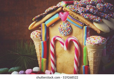 Festive Christmas Gingerbread House decorated with candy canes, marshmallow cones, chocolates and candy in a rustic dark wood setting, closeup with copy space, with applied retro style filters.