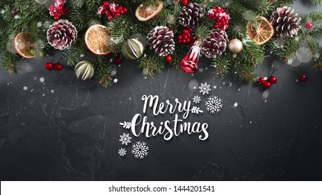 Festive Christmas greeting card with fir branches decorated with natural dried decor of oranges, lemons, fir cones and red berries. Dark black textured background with inscription merry Christmas.
