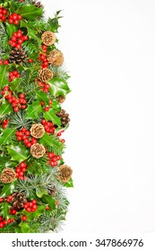 Festive Christmas natural holly  vertical border with bright red berries, pine and fir foliage and cones  over white with copy space for your seasonal greeting