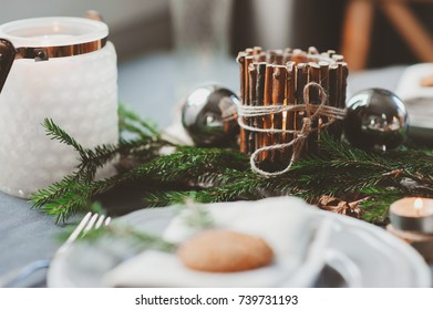 Festive Christmas and New Year table setting in scandinavian style with rustic handmade details in natural and white tones. Dining place decorated with pine cones, branches and candles