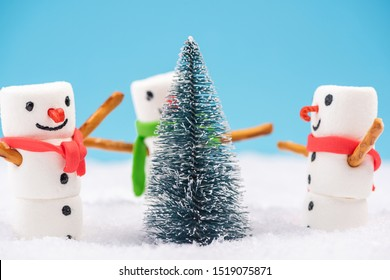 Festive Christmas Snowmans Dancing Around Christmas Tree in Snow.