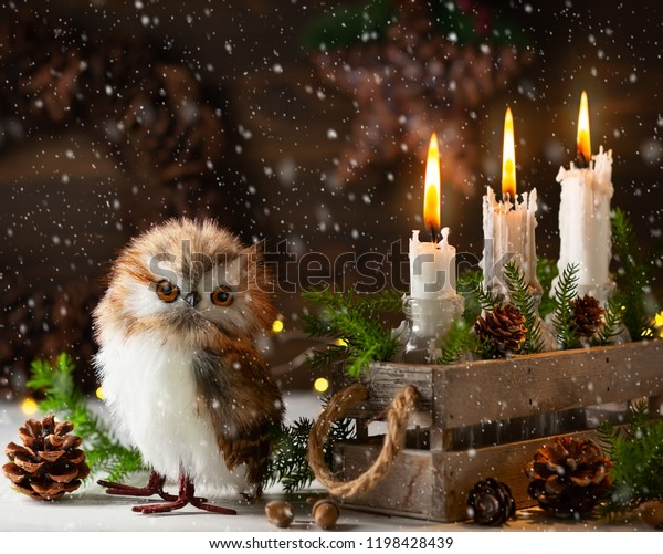 Festive Christmas still-life arrangement of candles,owl, pine cones and fir branches in old box on a rustic wooden background