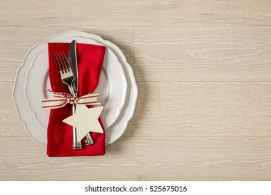 Festive Christmas table setting place setting with white china plates, red cloth napkin and silverware on rustic wood background. Horizontal with empty blank space on right.